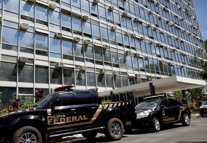 Pie Vehículos de la policía federal, frente al ministerio de Agricultura durante el operativo Carne Débil, en Brasilia. (Reuters)