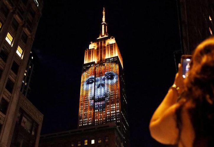 Una mujer fotografía el Empire State Building en cuya fachada se proyecta la imagen de una especie protegida en Nueva York, Estados Unidos. (EFE)