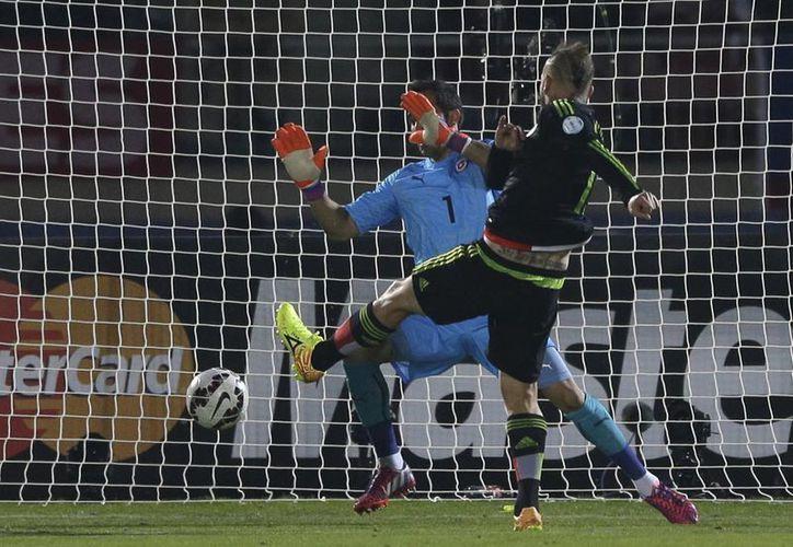 Matías Vuoso de forma dramática alcanza a puntear el esférico para anotar uno de sus dos goles ante Chile en Copa América. (Fotos: AP)