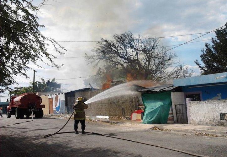 Un tragahumo lanza chorros de agua con la manguera para acabar con el fuego en la colonia Emiliano Zapata Sur III. (Milenio Novedades)