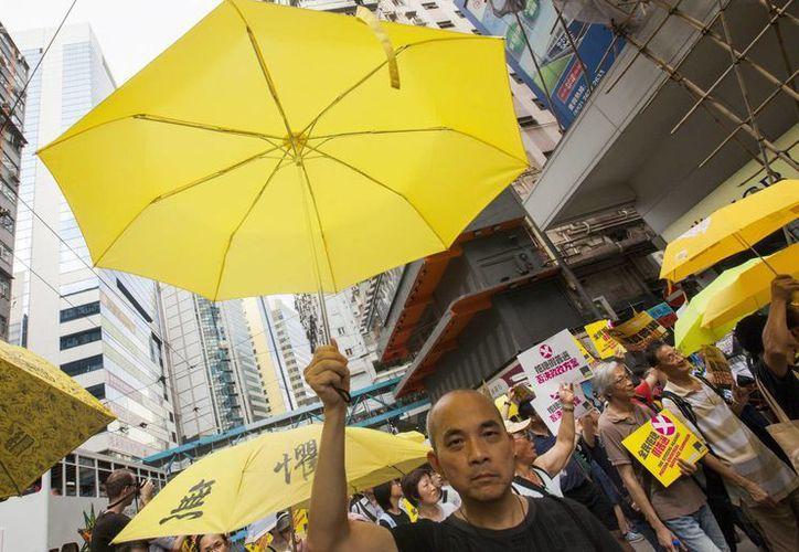 Manifestantes a favor de la democracia caminan por una calle del centro de Hong Kong para apoyar la eliminación de una reforma electoral respaldada por Beijing que provocó protestas callejeras masivas el año pasado. (EFE)