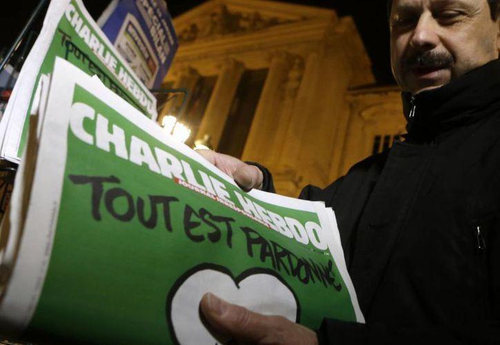 Un vendedor de periódicos instala ejemplares de Charlie Hebdo en un estante en un quiosco en Niza, el sureste de Francia. (Agencias)