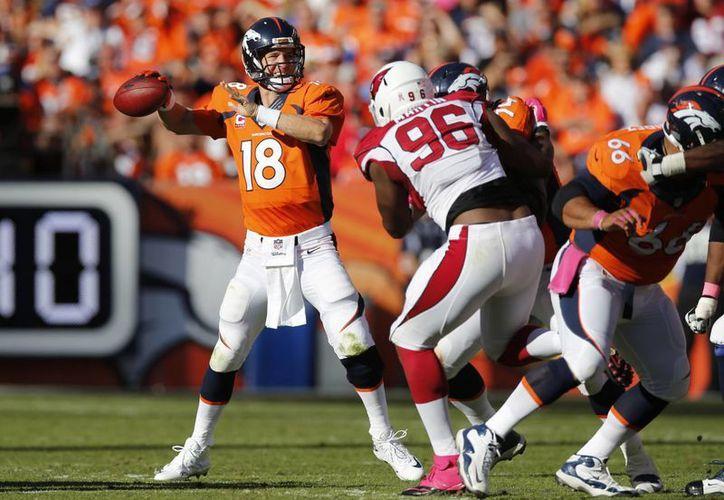 El quarterback de Broncos de Denver, Peyton Manning (18), se dispone a lanzar mientras Kareem Martin (96), defensivo de Arizona Cardinals, intenta evitarlo. (Foto: AP)