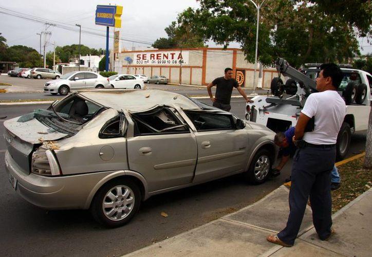 El Corsa de Kenny Chan quedó muy dañado al caerle encima un árbol en Paseo de Montejo. (Jorge Pallota/SIPSE)