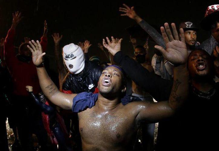 Los residentes de Ferguson continuaron manifestándose pese al toque de queda decretado desde el pasado viernes. (AP)
