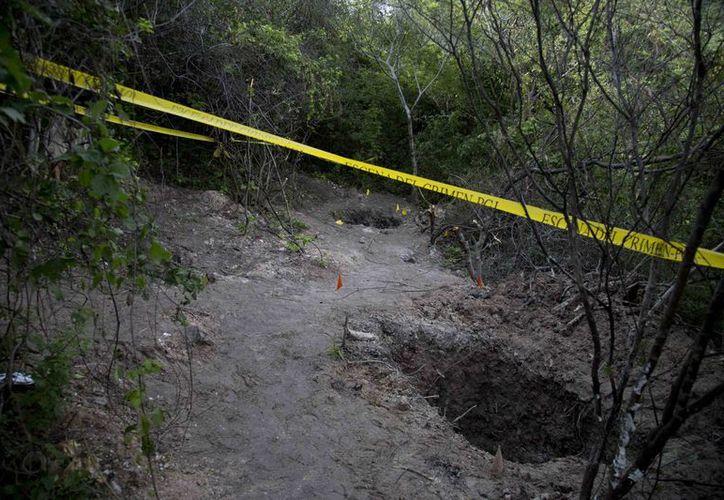 El procurador de Guerrero dijo que los asesinos hicieron camas de ramas y colocaron encima los cadáveres para prenderles fuego. (AP)