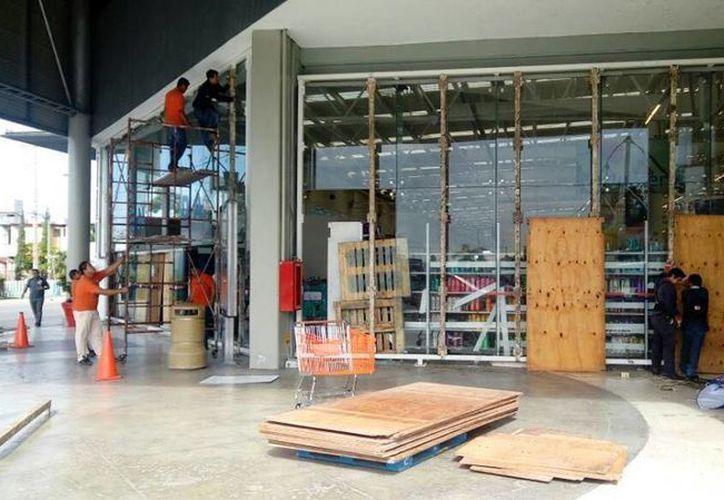 Colocan tablas resistenten en supermercados ante posibles saqueos. (Alejandra Galicia/SIPSE)