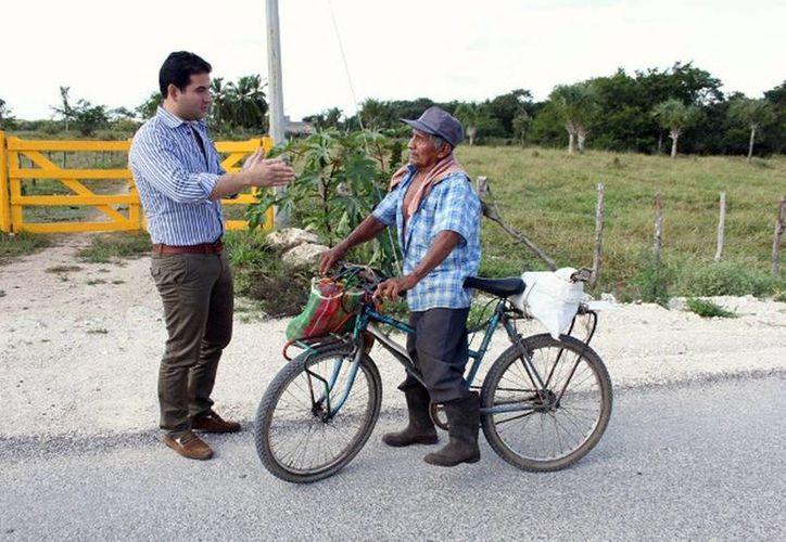 El recorrido de Tizimín- Chenkekén se realizaba en 1:20 horas; hoy puede hacerse en 45 minutos. Imagen de Javier Osante Solís mientras platica con el campesino Lorenzo Chi. (Milenio Novedades)