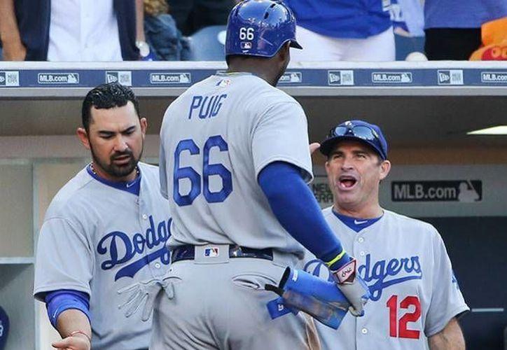 Dodgers venció 15 a 0 a Padres de San Diego en el juego inaugural de la Temporada 2016. En la foto, Adrián González felicita a Yasiel Puig a su llegada al dugout.(AP)