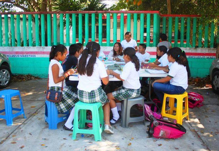 El lunes los estudiantes de la primaria Eduardo Pliego León tomaron clases en el estacionamiento del plantel, en apoyo a su maestra despedida. (Daniel Pacheco/SIPSE)