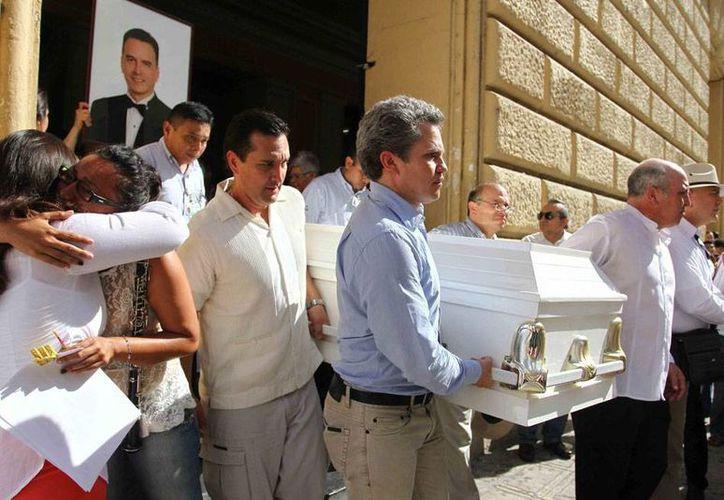 """Tras recibir un homenaje en el teatro José Peón Contreras, el féretro de Luis Luna Guarneros, seguido por sus familiares que se turnaban a ratos para cargar la fotografía de """"el maestro"""", fue llevado hasta la Iglesia de Monjas, para una misa de cuerpo presente. (Notimex)"""