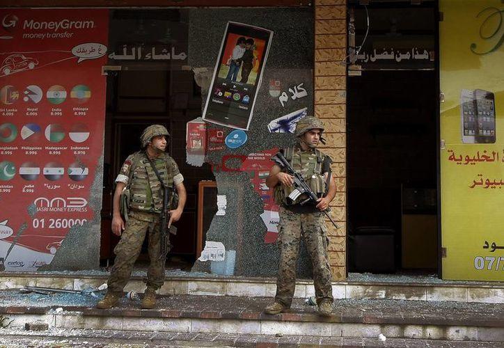 Soldados libaneses hacen guardia frente a una tienda destrozada tras un ataque. (Archivo/EFE)