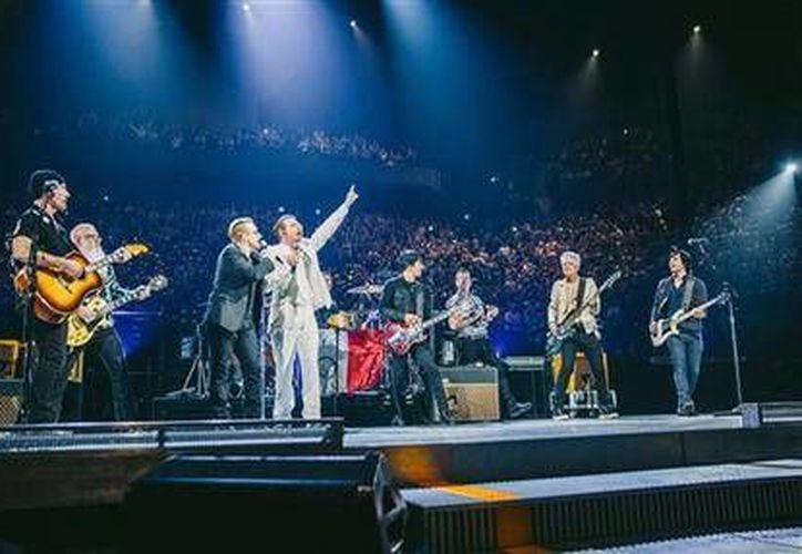 Miembros de Eagles of Death Metal aparecieron de sorpresa en su primera presentación pública desde los ataques del 13 de noviembre que cobraron 113 vidas alrededor de la ciudad. En la imagen, U2 y la banda Eagles of Death Metal tocan juntas el pasado 7 de diciembre, en París, previo a los atentados. (AP)