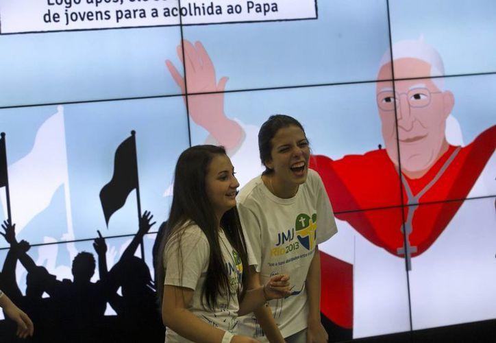 Peregrinas rién frente a una pantalla que muestra un dibujo del papa Francisco en el aeropuerto internacional de Río de Janeiro, Brasil. (Agencias)