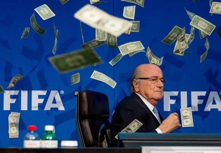 Antes de iniciar su conferencia de prensa, Josep Blatter fue atacado por el comediante inglés Lee Nelson quien le aventó billetes falsos a la cara del suizo. (AP)