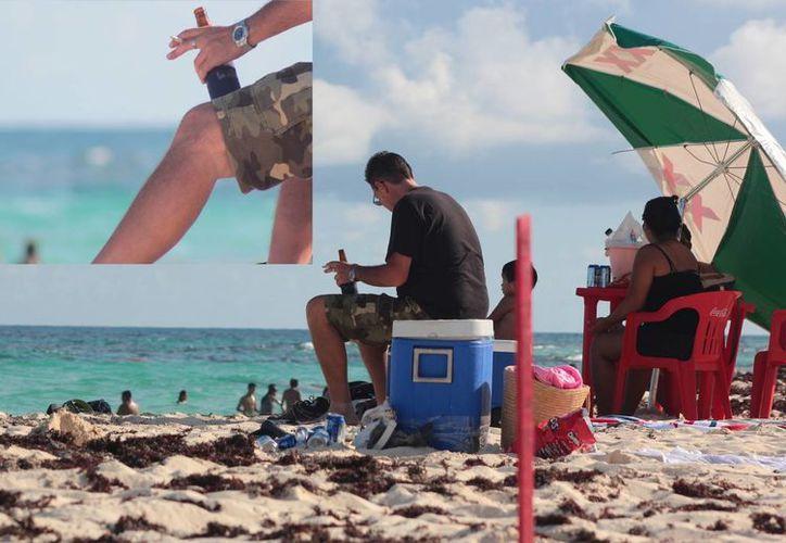 """Los visitantes de la playa San Martín consumen cigarros sin tomar en cuenta los letreros que advierten que es la única del país nombrada como """"libre de humo de tabaco"""".  (Gustavo Villegas/SIPSE)"""