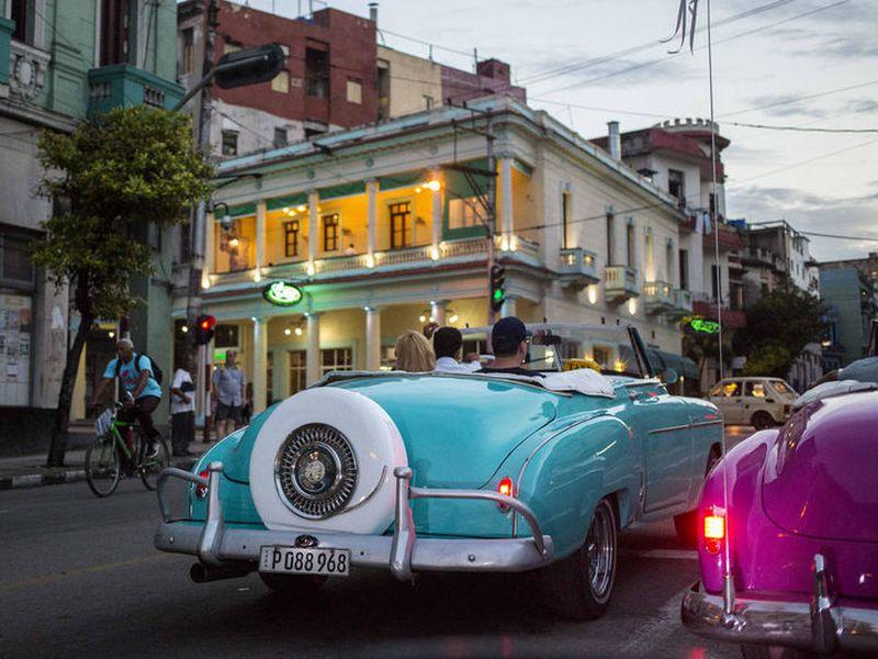 Tourists ride classic American convertibles in Havana, Cuba.