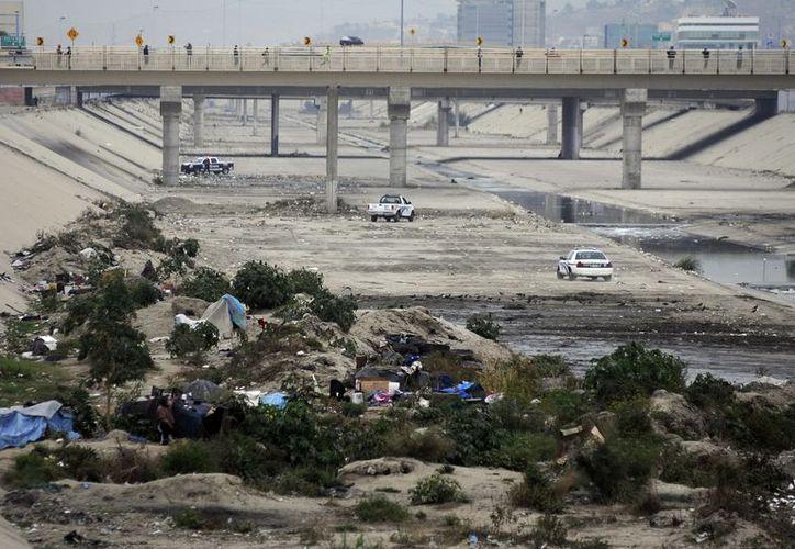 Decenas de migrantes huyeron por un operativo que realizó la policía municipal, en la canalización de Río Tijuana. (Archivo Notimex)