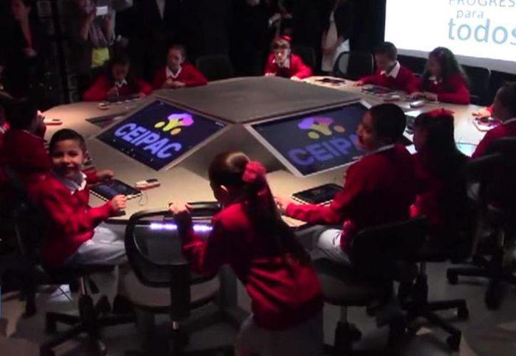 Los alumnos, vestidos con camisa blanca y suéter rojo, se sientan alrededor de una estructura metálica a la que llaman 'estación central'.(twitter.com/XHespanol)