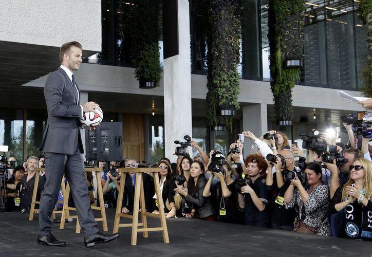 Beckham durante su llegada a una rueda de prensa en Miami. Anunció que uno de sus socios para comprar un equipo y colocarlo en la MLS es el basquetbolista LeBron James. (Agencias)