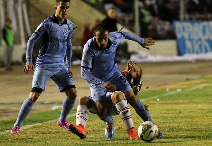 José Luis Sánchez Capdevila, del Bolívar de Bolivia (frente), disputa el balón con Héctor Villalba (atrás) de San Lorenzo de Argentina, durante el partido de vuelta por la semifinal de Copa Libertadores en el estadio Hernando Siles de Bolivia. (EFE)