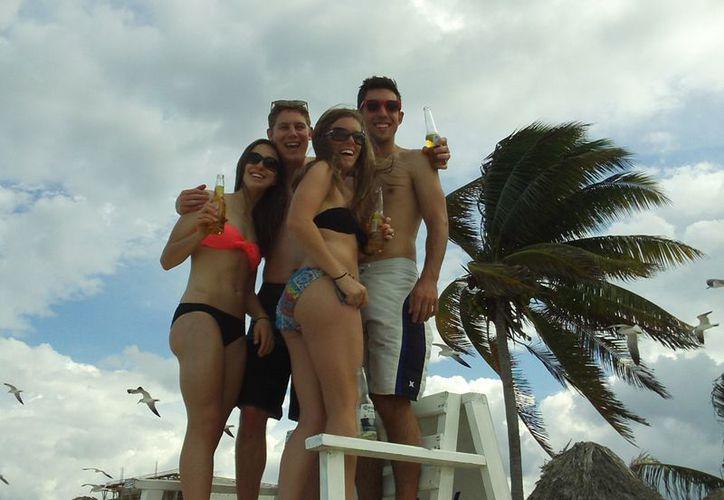 Turistas bailando animadamente en una silla elevada, en el malecón de Progreso. (Manuel Pool/SIPSE)