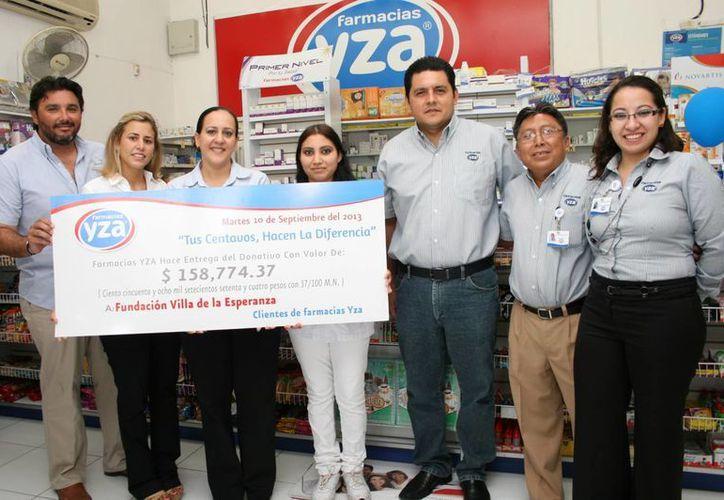 Directivos de Farmacias Yza y de Fundación Villa de la Esperanza durante la entrega del donativo. (SIPSE)