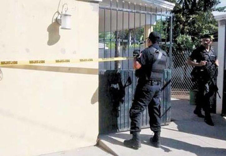 Policías en una de las casas que fueron decomisadas ayer a la banda criminal en Michoacán. (Milenio)