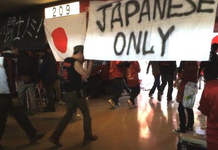 Esta es la pancarta con la frase Only Japanese (Solo japoneses) puesta por seguidores del club Urawa Reds. (Milenio/twitter)