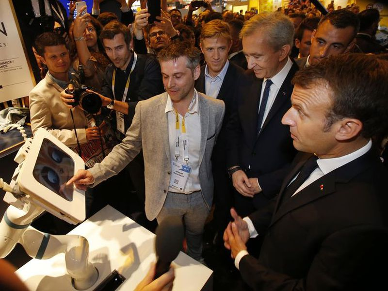 CEO of Spoon.ai Jerome Monceaux, left, points to a screen as he talks to LVMH luxury group CEO Bernard Arnault, center, and French President Emmanuel Macron as they visit the VivaTech gadget show in Paris.