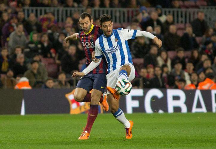 Carlos Vela -quien en la imagen disputa un balón durante un partido de su club, Real Sociedad, contra el Barcelona- llegó a la concentración de la Selección Mexicana. (Archivo/NTX)