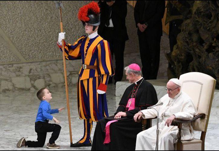 Wenzel Eluney, un niño niño autista juega con un guardia suizo en el salón Pablo VI en el Vaticano. (Foto: AP)