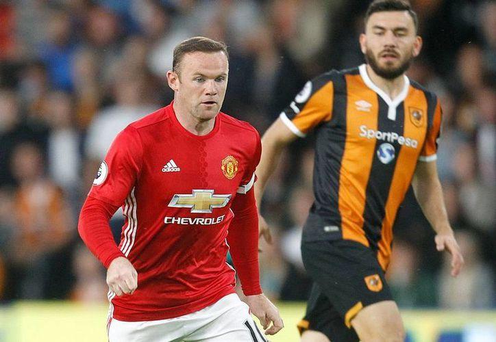 Wayne Rooney (izq.), delantero de la Manchester United, y de la Selección de Inglaterra, y quien funge como capitán de ambas escuadras, anunció su retiro de las canchas. (Archivo/AP)