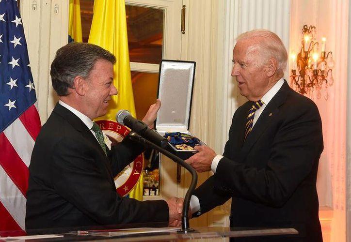 El presidente de Colombia, Juan Manuel Santos, le entregó la condecoración a Joe Bide, vicepresidente de EU, durante una cena de homenaje. (facebook.com/JMSantos.Presidente)