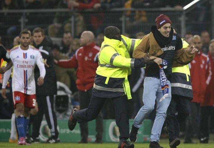 Un aficionado (d) alcanzó a golpear con su bufanda al mediocampista Franck Ribery antes de ser detenido en el partido de Copa de Alemania entre Bayern y Hamburgo. (Foto: AP)