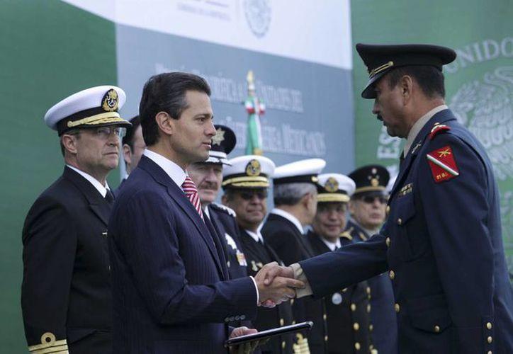 El presidente Enrique Peña (c) durante las distinciones a unidades y personal de la Defensa, Marina y Fuerza Aérea. (Notimex)