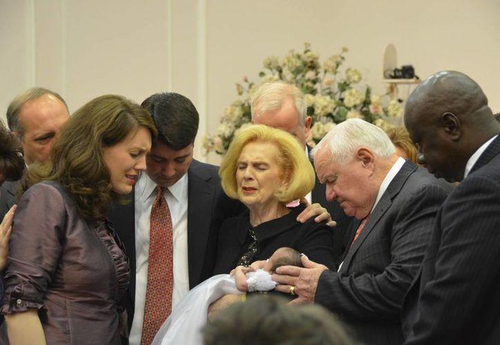 Fotografía de 2012 facilitada por un exmiembro de la iglesia Word of Faith Fellowship en la que aparece la líder de la orden Jane Whaley (c) sosteniendo un bebé y acompañada de su esposo, Sam (centro, a la derecha) y otras personas durante una ceremonia en un templo en Spindale, Carolina del Norte. (AP)