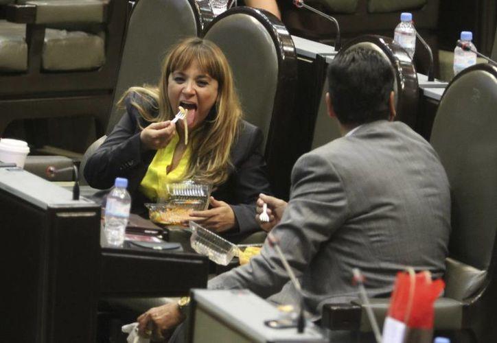 La legisladora federal Flor Ayala Robles se alimenta en su curul durante la sesión en el palacio Legislativo de San Lázaro. (Notimex)
