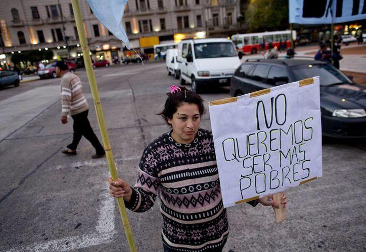 """Una mujer sostiene un cartel que dice """"No queremos ser más pobres"""" en una protesta ante el Congreso, cerca de un comedor popular en Buenos Aires, Argentina. (AP/Natacha Pisarenko)"""