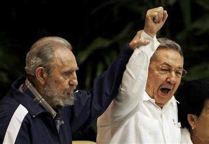 Fidel Castro levanta la mano a su hermano Raúl, el 19 de abril de 2016, en el Congeso del Partido Comunista, en La Habana. Una de las últimas apariciones en público de Fidel, fallecido el viernes 25 de noviembre de 2016. (Archivo/AP)