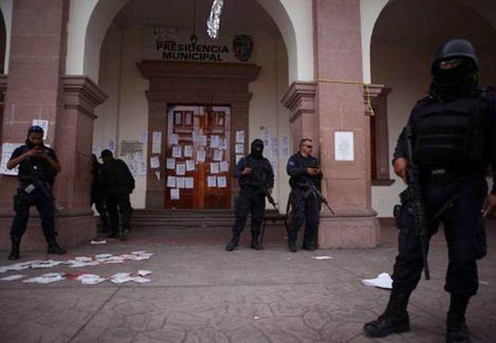 La madrugada del martes, la Policía Federal y el Ejército realizaron un operativo para desalojar el palacio municipal de Apatzingán, el cual dejó 9 muertos y 44 detenidos. (Milenio)