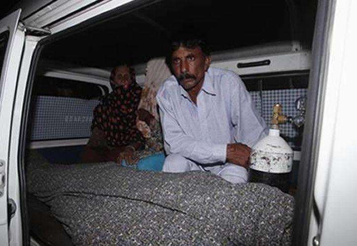Mohammed Iqbal, a un costado del cadáver de su fallecida esposa, Farzana Parveen. (Reuters)