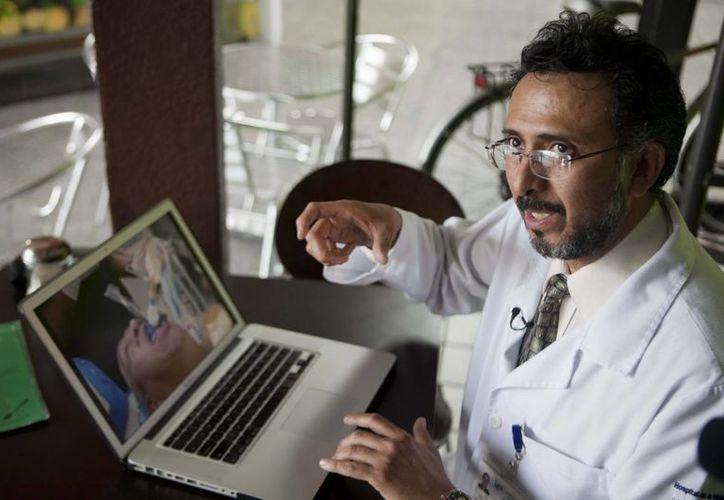 El médico Juan Mandujano Guajardo muestra en su laptop imágenes del paciente tomada para hacer la foto de Hugo Chávez. (AP)