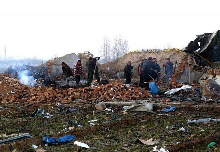 Gente camina entre los escombros de una fábrica de fuegos artificiales destruida en la provincia de Henan, China. Varias personas murieron y siete resultaron heridas este jueves por el estallido en la fábrica. (Chinatopix vía AP)
