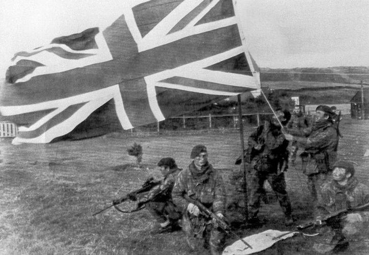 Soldados de la Marina Real izando la bandera de Gran Bretaña en Puerto Howard en el oeste de las ïslas Malvinas en 1982. (EFE)