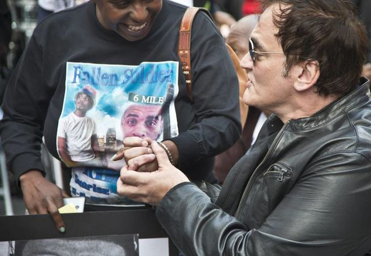 Policías de Estados Unidos dicen que le tienen preparada una sorpresa al cineasta Quentin Tarantino, quien criticó la brutalidad policiaca y quien en la foto, durante una manifestación, sostiene la mano de una mujer que perdió a su hijo en un hecho policiaco. (AP)