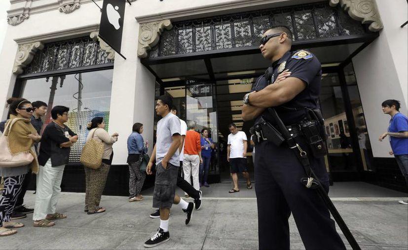 Un policía vigila la entrada de la tienda de Apple. (Agencias)
