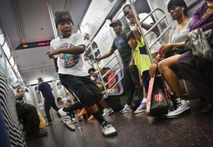 Un niño de ocho, miembro de la troupe de baile W.A.F.F.L.E., actúa en un tren del metro de Nueva York. (Agencias)