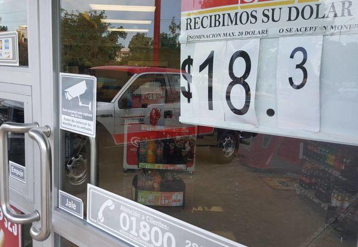 Algunos comercios publican cuál es el valor del dólar en pesos. (Jesús Tijerina/SIPSE)