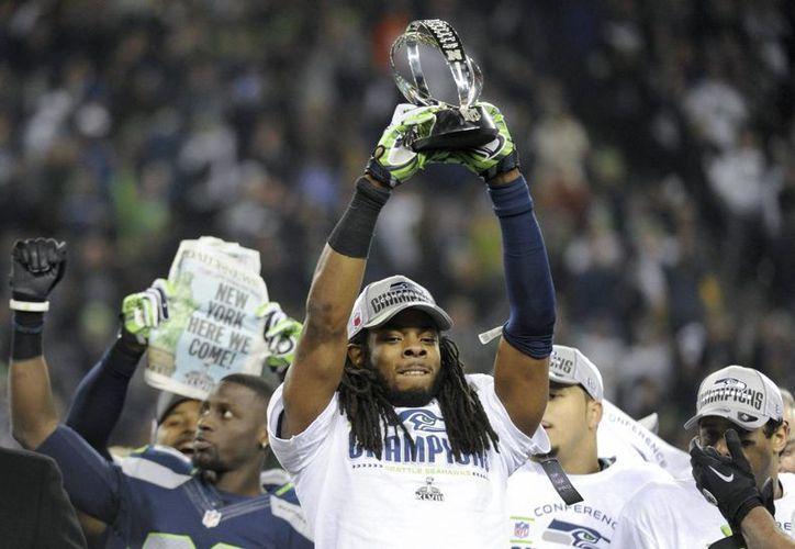 El jugador de los Seahawks de Seattle, Richard Sherman, sostiene el trofeo de la Conferencia Nacional (NFC). (EFE/Archivo)